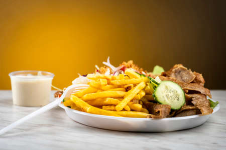 kebab meat with fries and vegetables - takeaway