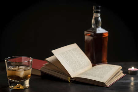 a glass of whiskey and a good book - time to relax - photo in retro style