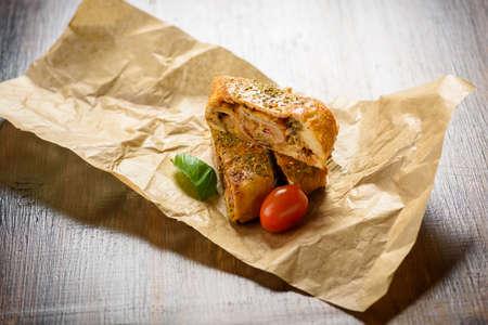 Pizza stromboli on a wooden background
