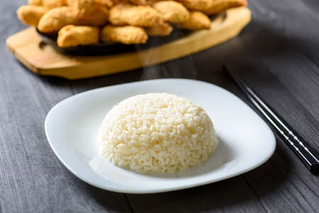 hot rice serving on a white plate on wooden table