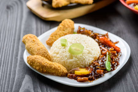 rice with vegetables in sweet and sour sauce and chicken tenderloin on white plate