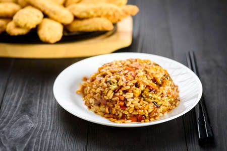 rice with vegetables in sweet and sour sauce on wooden table