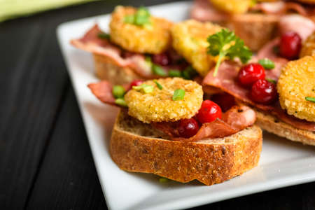 sandwich with fried camembert cheese, bacon and cranberries Stock fotó
