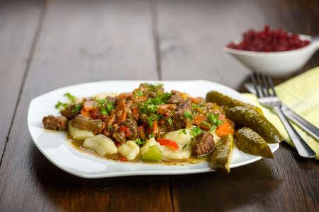 potato dumplings with goulash and cucumber