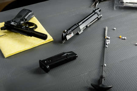 Cleaning the gun is an important part of ASG games. A working weapon is an element of a successful game. Disassembled pistol on a wooden table.