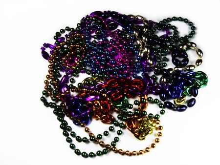 Strands of Mardi Gras beads in various colors on white background. photo