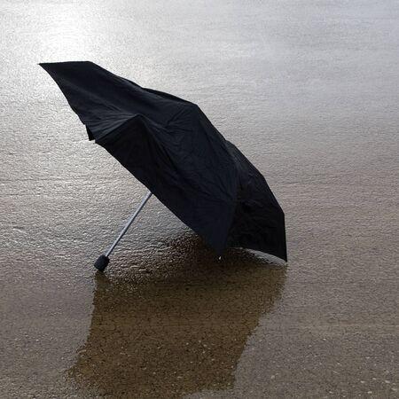 tremp�e: Parapluie noir cass� sur la pluie imbib� b�ton