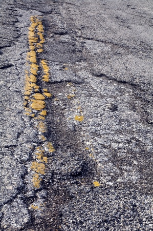 striping: Texture of cracked and worn, broken, asphalt on county road retains some yellow striping