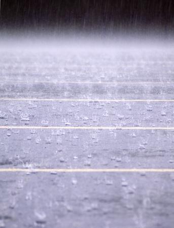 Raindrops splash on a parking lot in a downpour  photo
