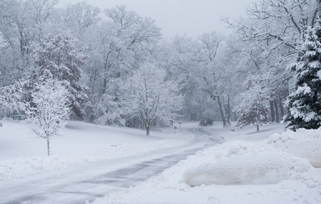 snow plow: Snow plow clears roads as snow falls in park  Plowed snow in foreground  Stock Photo