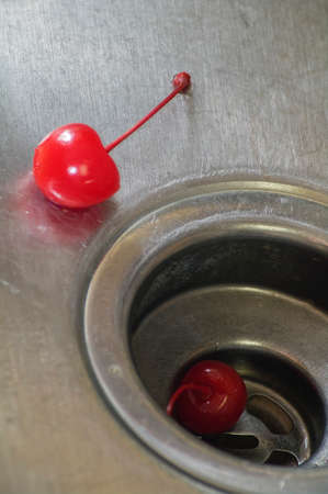 scratches: Two wet red cherries in scratched stainless steel sink.