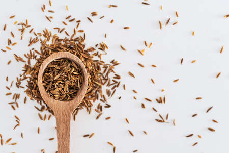 Cumin grain in a spoon composition on a white background. Cumin close up texture. Macro lens.