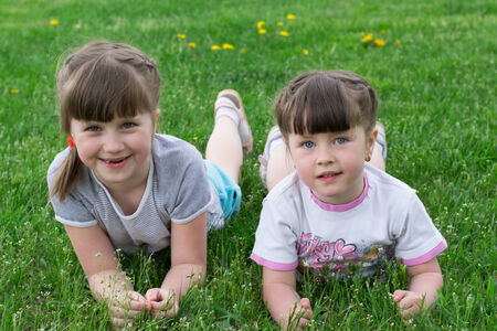 Two funny sisters lay on the grass photo