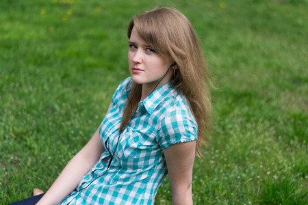 Girl listening to music with headphones while sitting on the grass photo