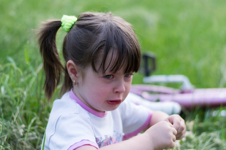 Little girl cries much sitting in the grass photo