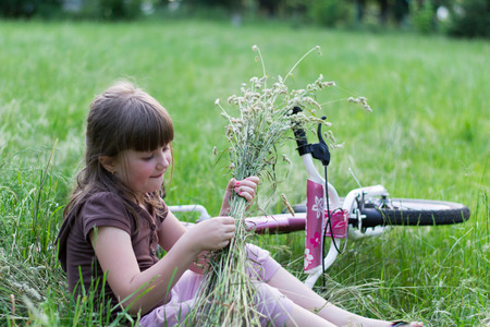 Little girl with bicycle sitting in the grass photo