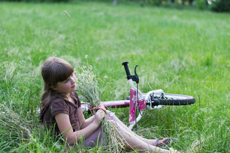 Girl in the grass with a bicycle and a bouquet of herbs photo