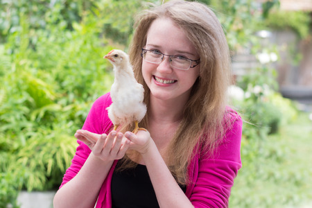 cheerful girl with a small chicken in his hands photo