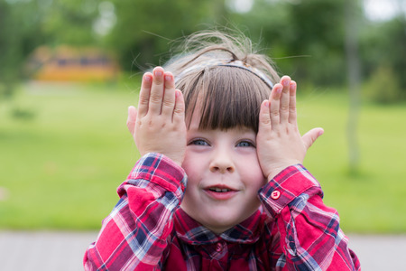 Surprised little girl with hands on face, outdoors, closeup photo