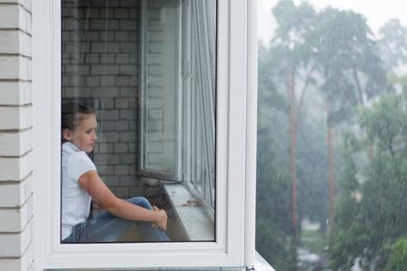 fille triste: triste fille � la fen�tre d'un immeuble de plusieurs �tages