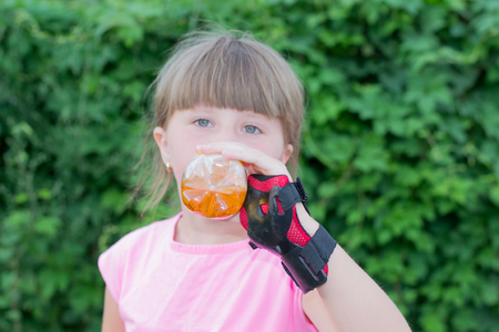 girl drinking from a bottle of lemonade, Outdoors photo