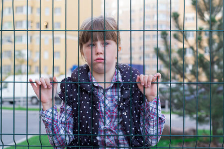 sad little girl looking through a fence photo