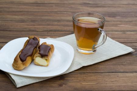 choux: pasta choux con el chocolate y una taza de t� Foto de archivo