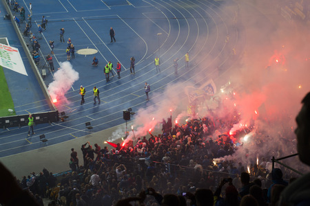 football fans celebrate victory with fireworks during a football match