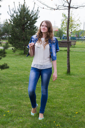 teen feet: Young cheerful girl in blue jeans with sunglasses in hand, outdoors, in full length, standing on the grass Stock Photo