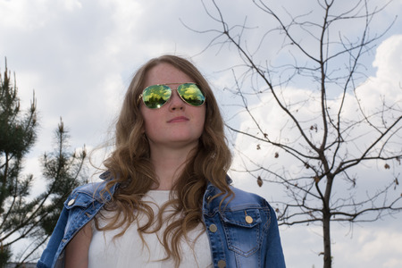 looking ahead: Young cheerful girl in sunglasses, close-up, outdoors, looking ahead and up