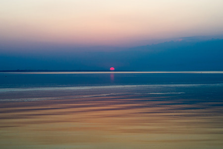 horizon reflection: bright blue sunset with reflection in sea surface at the time of contact with the horizon