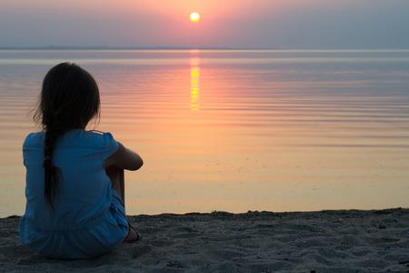 horizonte: niña sentada en la playa en un ligero vestido de verano, viendo la puesta de sol en el mar en el horizonte