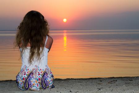 mujer mirando el horizonte: niña sentada en la playa en un ligero vestido de verano, viendo la puesta de sol en el mar en el horizonte