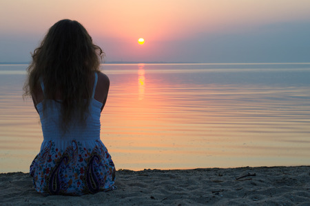 여자는 수평선에 바다로 설정 태양을보고, 가벼운 여름 드레스에 해변에 앉아 스톡 콘텐츠