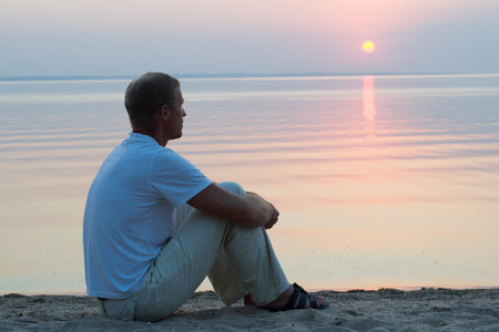 over the horizon: a man sitting on the beach in white pants and a white t-shirt, watching the sun set into the sea on the horizon Stock Photo