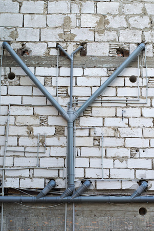 building wall: modern plastic pipes on the back wall of a two-storey old building