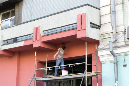 in jeans and a work shirt facade paint roller standing on the scaffolding