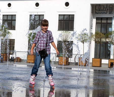 wet jeans: little girl 8 years in wet jeans and shirt riding on roller skates in the fountain in the summer park