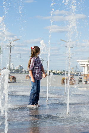 wet jeans: little girl 8 years in wet jeans and shirt playing in the fountain in the summer park