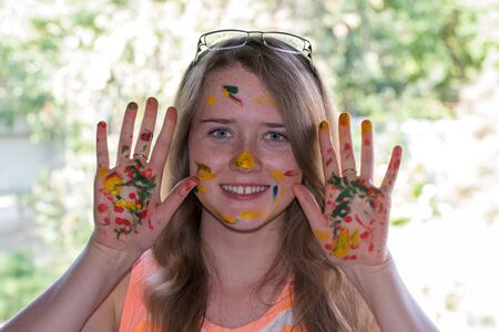 face paint: cheerful girl holding hands stained with paint stained face paint Stock Photo