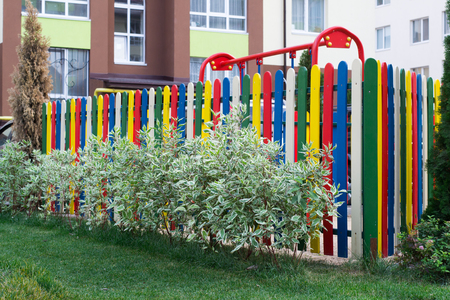 fenced in: colorful playground is fenced by a fence in a small green park with shrubs and trees in urban areas
