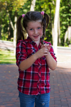 ponytails: cheerful girl in jeans and a red shirt in the box is in the park braids and ponytails pigtails