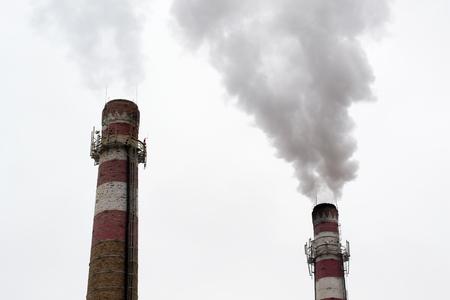 smokestacks: two brick smokestacks with black smoke