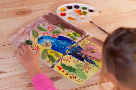 colores calidos: La muchacha drena una gran aguada loro en el papel en colores c�lidos Foto de archivo
