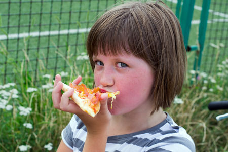 eyes wide open: little girl with her eyes wide open with delight eating pizza in the summer park