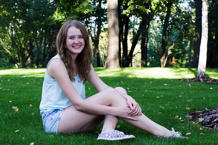 young girl with a smile in short shorts sitting on the grass in the park close up in summer