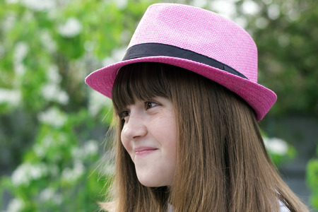 Portrait of a small cheerful, happy girl with a smile in a pink summer felt hat against a close-up nature background