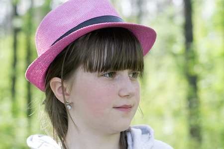 Portrait of a small  girl with a smile in a pink summer felt hat against a close-up nature background