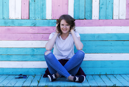 A young girl with a smile, in jeans, sneakers, a white T-shirt and holds hands in her hair, sits on colorful boards