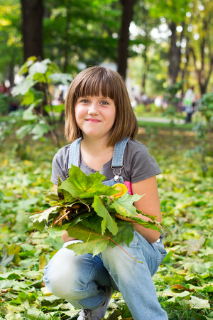 Portrait of a little cheerful, happy girl with an armful of autumn colorful leaves in the park  Stock Photo